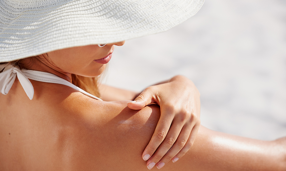Woman in hat rubbing suncreen on her shoulder