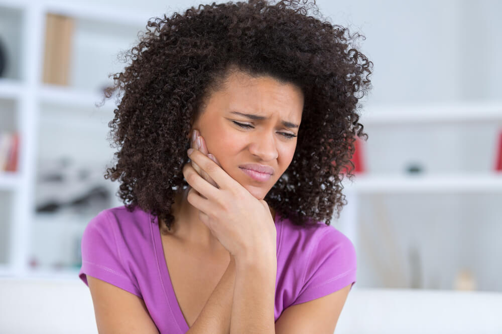 Woman holding painful jaw