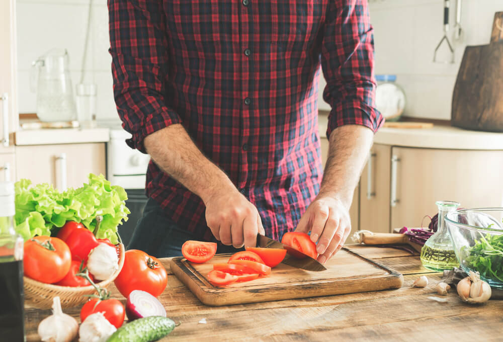 Man chopping tomatoes in kitchen