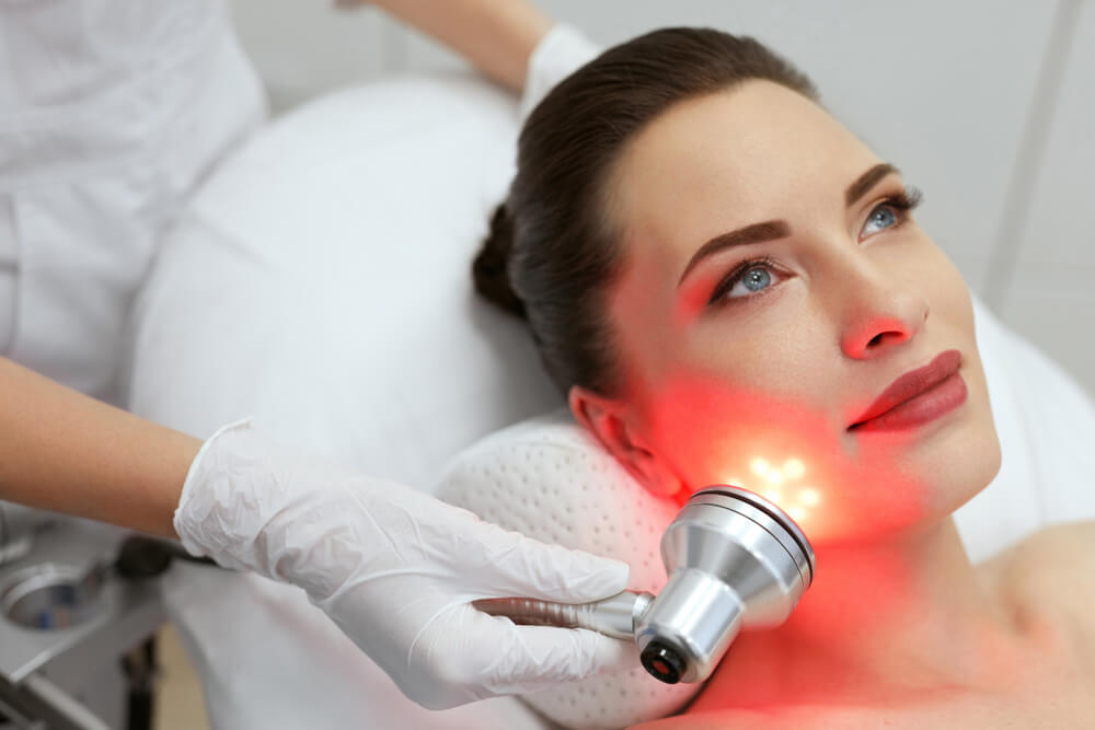 Woman having LED therapy on face
