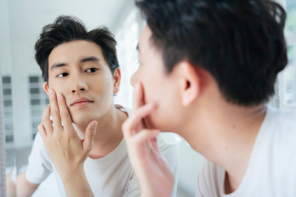 Man looking at skin in mirror