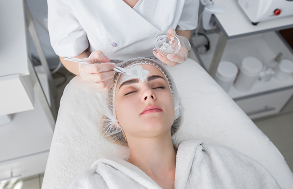 Esthetician applying gray facial mask on client