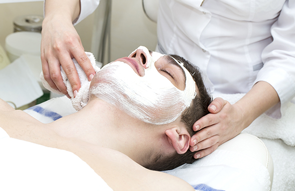 Facialist wiping face mask off male client's face