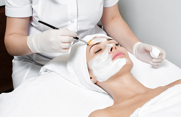 Facialist applying face mask on client