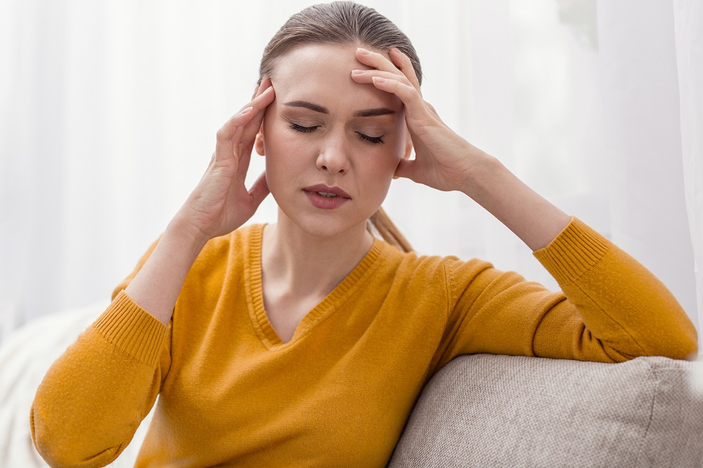 woman holding her hands over her head looking stressed