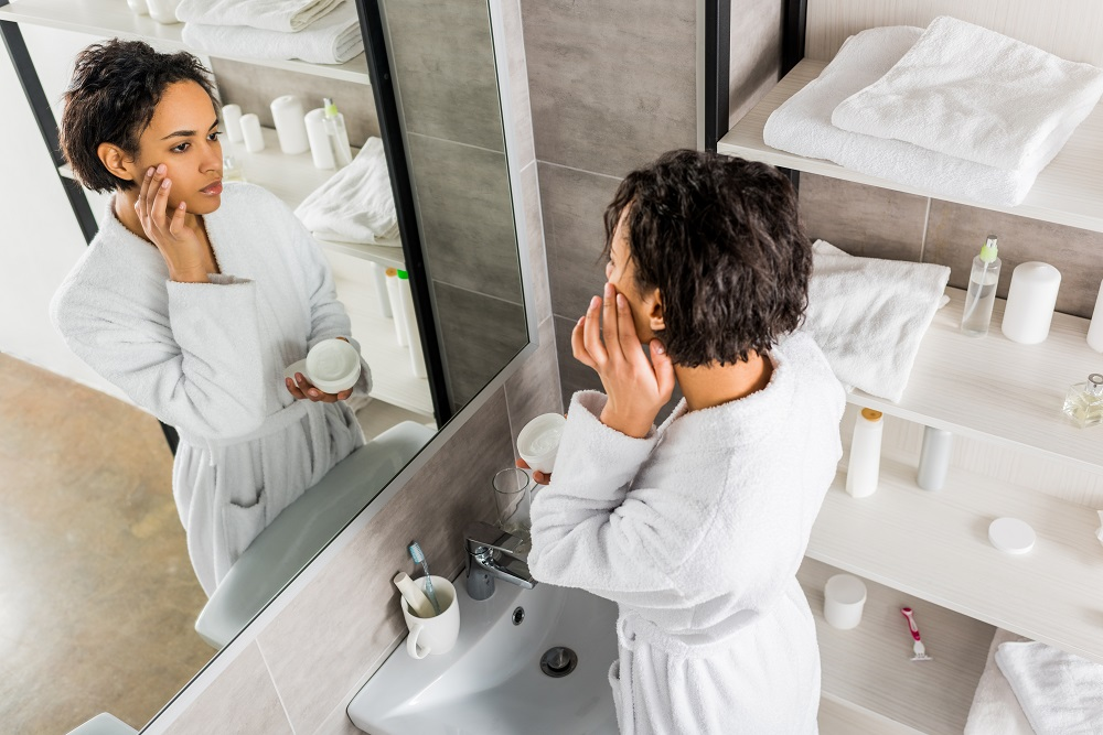 woman applying face cream in the mirror