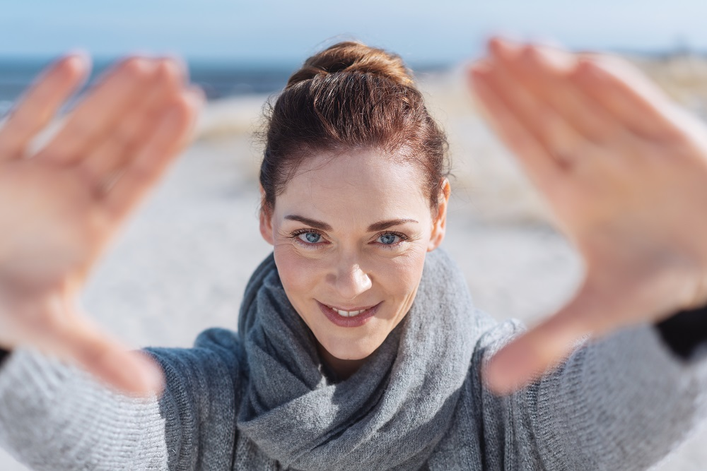 mid-30s woman holding hands up to frame face