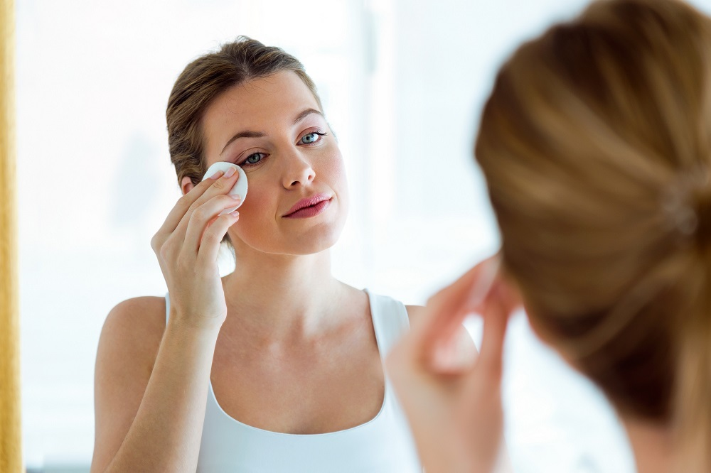 woman in mirror removing eye makeup